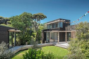 View from garden to wooden terrace with pergola outside modern house