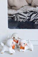 Three kitschy china lambs wearing bows
