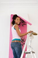 Young woman on ladder hanging wallpaper