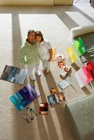 Happy couple standing amongst colour charts
