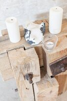 White candles and stone on rustic wooden sculpture