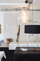 Black lampshade above perforated sheet metal table in loft apartment with brick wall