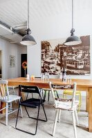 Wooden table, various chairs and black pendant lamps in front of large vintage-style photo