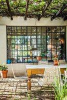 Mediterrane Terrasse mit Blick durch Sprossenfenster