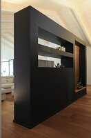 Black partition wall with shelves and apertures