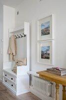 Weisser Garderobenschrank mit Kissen und Kleiderhaken neben gerahmten Fotos