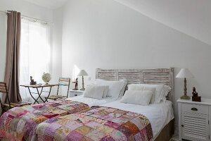 Doppelbett mit Betthaupt, Patchworkdecken und Vintage Gartentisch mit Klappstühlen vor Fenster
