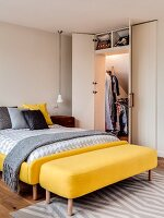 Bed with yellow upholstered frame next to open fitted wardrobe under sloping ceiling