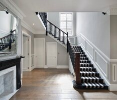 Striped carpet on stairs in hallway with mouldings on walls