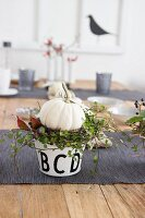 Autumnal arrangement of white pumpkin and wreath of leaves in pot decorating table