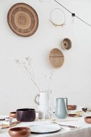 Wooden bowls on set table and decorations on wall made from natural materials
