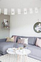 Graues Ecksofa und weisse Tabletttische in Wohnzimmer mit nordischem Flair