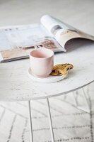 Becher mit Keks und Zeitschrift auf weissem Tabletttisch