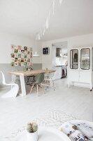 Esstisch mit rustikaler Holzplatte und verschiedene Klassikerstühle vor Retro Wandbild, Vitrinenschrank neben dem Durchgang zur Küche