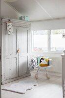 Hellgrauer Vintage Kleiderschrank und Klassiker-Schaukelstuhl am Fenster im Dachzimmer