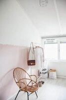 Rattanstuhl und weisser Kleiderständer mit Damenbekleidung im Dachzimmer