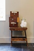 Three old drawers and sweet jar on stool