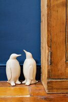 Two white penguin figurines on wooden floor against blue wall