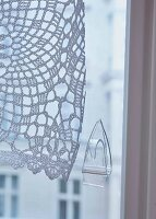 A transparent sticky hook on a window to hold a crocheted curtain