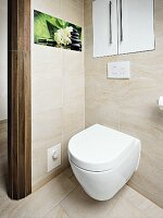 A white toilet under a built-in cupboard and photo art on a tiled wall
