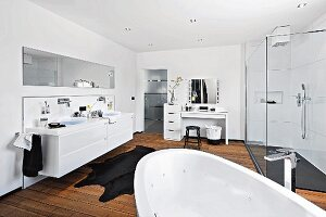 A bright white bathroom with a wooden floor, make-up table and shower area with glass panels