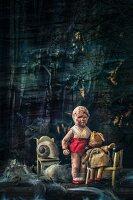 Macabre arrangement of dolls, dolls' furniture and feathers arranged against dark background