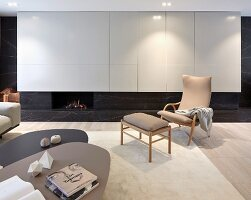 Set of coffee tables, armchair with wooden frame and matching footstool in front of white fitted cupboards with integrated gas fireplace