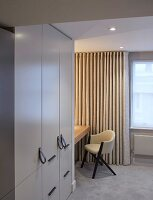 Fitted wardrobe with leather strap handles and chair in front of floor-length curtains on window