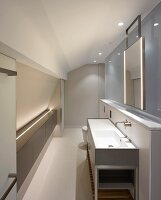 Washstand against half-height wall and frosted glass partition in modern attic bedroom