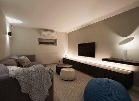 Long, low sideboard, indirect lighting and modern table lamp on floating shelf in elegant living room