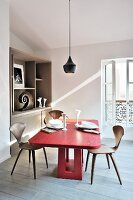 Red oak table and designer chairs below pendant lamp in dining room