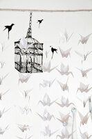 Mobile made from many white origami paper cranes hung from white wooden rod in front of black birdcage motif