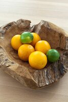 Oranges and limes in rustic wooden bowl
