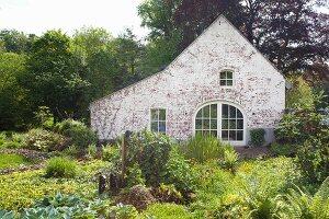 Traditionelles Landhaus mit Giebelfassade und Garten