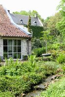 Garten mit Wasserlauf vor Terrasse und Fassadenausschnitt