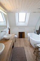 Modernes Designerbad mit freistehender weißer Badewanne und maßgefertigtem Waschtischmöbel in Dachgeschoss