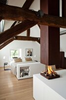Restored roof beams and open fireplace below suspended chimney in elegant white attic bedroom