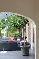 Lounge mit modernen, grauen Ledermöbeln in Wintergartenanbau