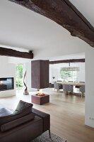 Offener Wohnbereich mit Kaminfeuer unter Kaminabzug in Designerambiente mit rustikalem Flair
