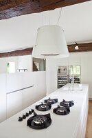 Weiße Küchenarbeitsplatte mit Gasherd und Dunstabzug in restauriertem Landhaus