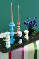 Turned wooden candlesticks in pastel shades and pansies on a vintage tray