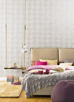 A double bed with a headboard and pillows next to a rustic swing used as a bedside table in front of grey patterned wallpaper