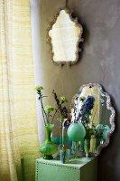 Arrangement mit Glasvasen, Blüten und Wandspiegel