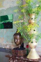 Künstlerische Vasenform mit Blütenstängel neben Buddhakopf in Vintage Ambiente