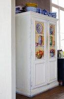 Weißer Vintage Schrank mit gemalten Kassettenfüllungen und blauem Geschirr