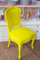Antique upholstered dining chair painted yellow in front of pink glass vessels and stacked white plates in white dresser