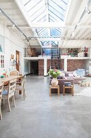 Open-plan eclectic interior in converted building with gallery and continuous ridge skylight