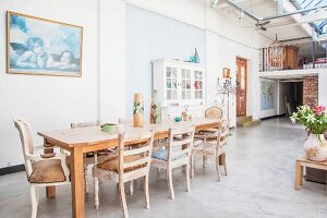 Vintage dining area on concrete floor and antique front door next to gallery
