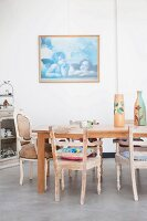 Vintage armchairs and dining table on concrete floor in front of framed picture of cherubs