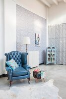 Antique blue leather armchair and vintage display cabinet on concrete floor in loft apartment with floral wallpaper